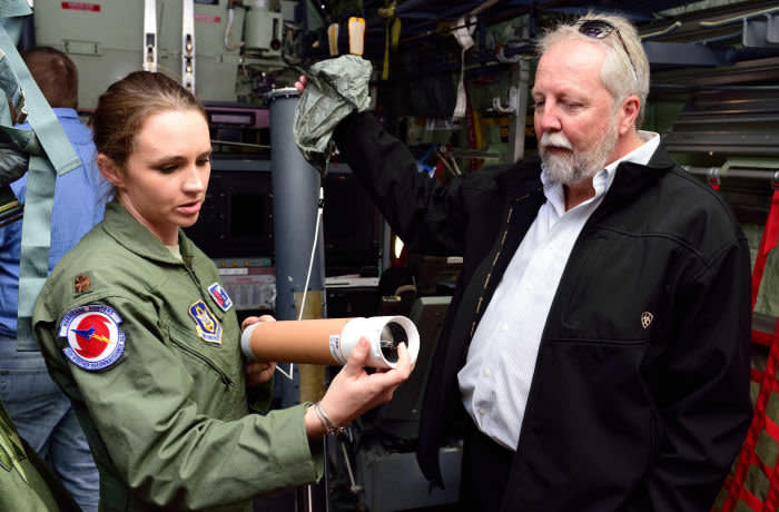 MKB9HB Maj. Ashley Lundry, 53rd Weather Reconnaissance Squadron aerial reconnaissance weather officer and chief scientific officer, shows a weather data-gathering instrument called a dropsonde to Dr. Fred ?Marty? Ralph, Researcher and Director for the Center of Western Weather and Water Extremes, Scripps Institute of Oceanography, Nov. 29, 2017, at Brown Field Airport, San Diego, California. Hurricane Hunters met with Ralph and other Scripps scientists that day to discuss plans for participating in atmospheric river reconnaissance missions in early 2018. (U.S. Air Force photo by Tech. Sgt. Ryan Labad
