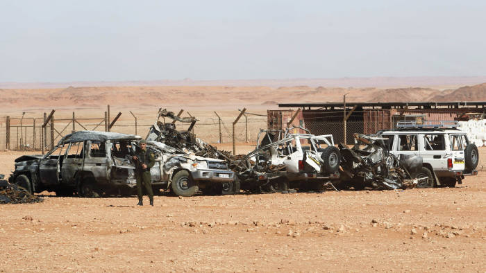 An Algerian soldier stands near damaged cars used by Islamist militants during a siege earlier this month near the Tiguentourine Gas Plant in In Amenas, 1600 km (994 miles) southeast of Algiers, January 31, 2013. REUTERS/Louafi Larbi (ALGERIA - Tags: MILITARY POLITICS CRIME LAW) - GM1E92106MP02