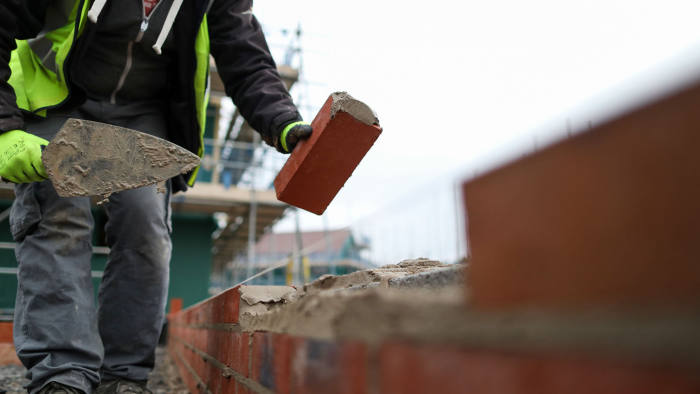 A builder lays bricks at a Persimmon Plc residential property construction site in Weston-Super-Mare, U.K., on Thursday, Jan. 26, 2017. Persimmon -- the U.K.'s largest homebuilder by market value -- designs, develops and builds residential housing units ranging from studio apartments to executive family homes throughout the United Kingdom. Photographer: Chris Ratcliffe/Bloomberg