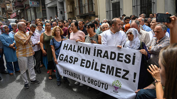 """Protesters hold a banner reading """"The will of the people , can not be usurped"""", as they take part in a demonstration in front of Peoples Democracy Party (HDP) headquarter, in Istanbul, on August 19, 2019. - The Turkish government removed three mayors from office on August 19, 2019 over alleged links to Kurdish militants, the interior ministry said. The mayors of Diyarbakir, Mardin and Van provinces in eastern Turkey -- all members of the Peoples' Democratic Party (HDP) elected in March -- were suspended. (Photo by Ozan KOSE / AFP)OZAN KOSE/AFP/Getty Images"""