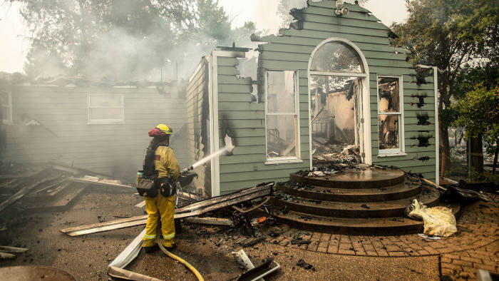 "A CalFire firefighter douses flames on a burning home during the Carr fire in Redding, California on July 27, 2018. - ""Two firefighters have been killed in the Carr fire. A private contractor (operating) a bulldozer died yesterday and a Redding City firefighter was killed in the evening,"" a spokesman for Calfire, the state's Department of Forestry and Fire Protection, told AFP. (Photo by JOSH EDELSON / AFP) (Photo credit should read JOSH EDELSON/AFP/Getty Images)"
