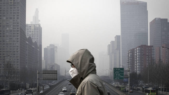 A man wearing a face mask walks on a footbridge as buildings shrouded in haze stands in the background in Beijing, China, on Friday, Jan. 6, 2017. Toxic haze that settled over much of China during the last three weeks has triggered a flight reflex among residents, leading to the rising popularity of smog avoidance travel packages to far-flung locations such as Iceland and Antarctica. Photographer: Qilai Shen/Bloomberg