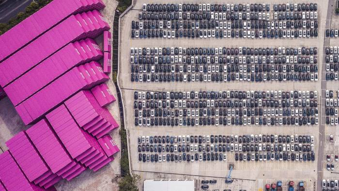 "Vehicles stand at a port in this aerial photograph taken above Shanghai, China, on Monday, April 30, 2018. China won't succumb to ""threats"" from the U.S., a senior government official said, hours before talks are set to begin Thursday with a delegation of the Trump administration's top trade policy officials. Photographer: Qilai Shen/Bloomberg"