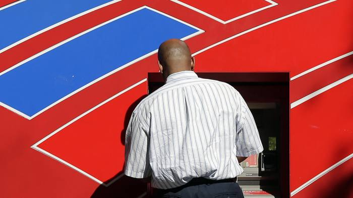 In this Thursday, April 13, 2017, photo, a man uses a Bank of America ATM near the company's headquarters in Charlotte, N.C. Bank of America Corporation reports earnings Tuesday, April 18, 2017. (AP Photo/Chuck Burton)
