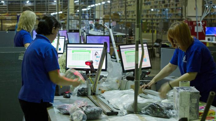 Workers scan products while preparing customers packages for shipping in the distribution center operated by Wildberries LLC, an online fashion retailer, in Podolsk, Russia, on Friday, July 13, 2018. Wildberries sells clothing and footwear, accessories, and cosmetics for women, men, and children in Russia. Photographer: Andrey Rudakov/Bloomberg