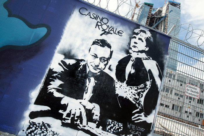 D7MNWK Graffiti with ECB President Mario Draghi and German Chancellor Angela Merkel is painted onto a fence at the construction site of the new European Central Bank (ECB) in Frankfurt Main, Germany, 10 May 2013. The painting and title are reminiscent of a James Bond Movie. Photo: BORIS ROESSLER