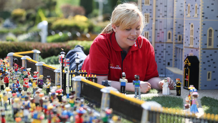Legoland employee, Lucy, poses putting a Lego model of US actress Meghan Markle (L) in place next to her husband-to-be Britain's Prince Harry (R) outside a Lego-brick model of Windsor Castle at Legoland in Windsor on May 8, 2018 during a photo call for its attraction celebrating the upcoming royal wedding. - Prince Harry and US actress Meghan Markle will marry on May 19 at St. George's Chapel at Windsor Castle. (Photo by Daniel LEAL-OLIVAS / AFP) (Photo credit should read DANIEL LEAL-OLIVAS/AFP/Getty Images)