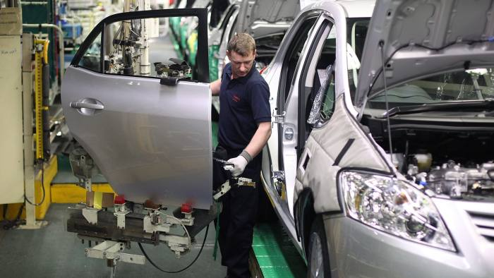 An employee attaches a door to a Toyota Motor Corp. automobile at the company's factory in Burnaston, U.K., on Friday, Feb. 18, 2011. Toyota Motor Corp. is aiming to post an operating profit at its parent company level on a monthly basis by the end of next fiscal year, said Executive Vice President Atsushi Niimi. Photographer: Simon Dawson/Bloomberg