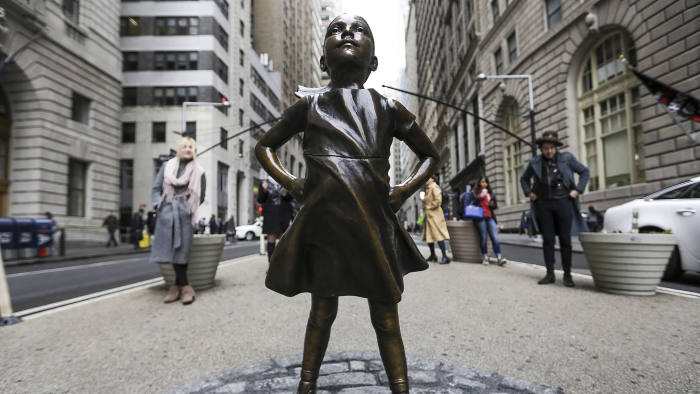 A statue of a defiant girl stands facing the Charging Bull sculpture in the Financial District of New York, U.S., on Wednesday, March 8, 2017. State Street Global Advisors, a nearly $2.5 trillion investor and unit within State Street Corp., installed the bronze statue in front of Wall Street's iconic charging bull as part of its new campaign to pressure companies to add more women to their boards. Photographer: Jeenah Moon/Bloomberg