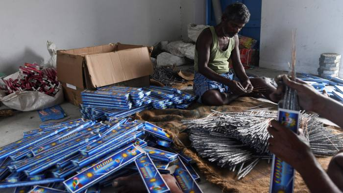 In this photograph taken on October 13, 2019, workers pack firecrackers in boxes at a manufacturing unit involved in the production of different varieties of firecrackers ahead of the Hindu festival of Diwali, in Sivakasi. - With thousands of workers painstakingly making by hand vast volumes of firecrackers, Sivakasi is usually at full tilt before Diwali. But with efforts to curb air pollution, India's $800-million pyrotechnics epicentre is fizzling out. (Photo by ARUN SANKAR / AFP) / TO GO WITH: INDIA-FESTIVAL-RELIGION-DIWALI-ECONOMY by Bhuvan BAGGA (Photo by ARUN SANKAR/AFP via Getty Images)