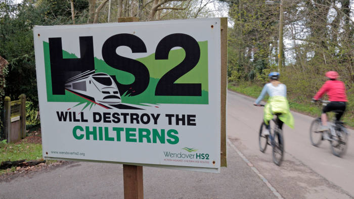CP0HXW Cyclists ride past an anti High Speed 2 (HS2-proposed railway) poster (Apr 2012) on a road close to Wendover, Bucks, UK.