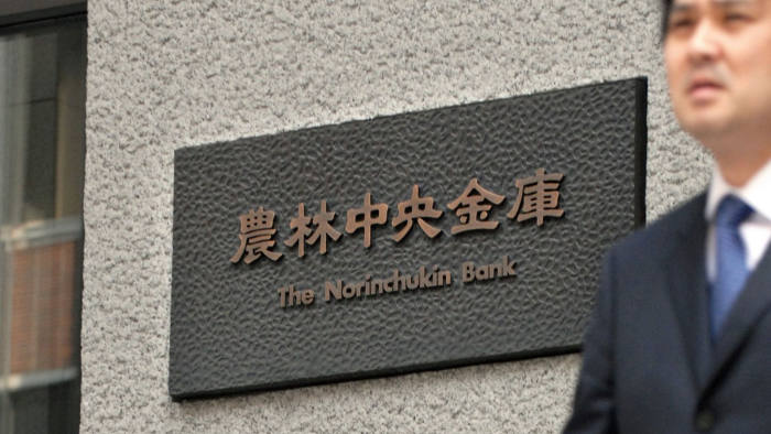 Businessmen walk past the offices of the Norinchukin Bank in Tokyo, Japan, on Friday, April 6, 2007. Norinchukin Bank Ltd., the country's largest holder of savings after Japan Post, is considering buying Nikko Principal Investments Japan Ltd. from Nikko Cordial Corp. Photographer: Robert Gilhooly/Bloomberg News