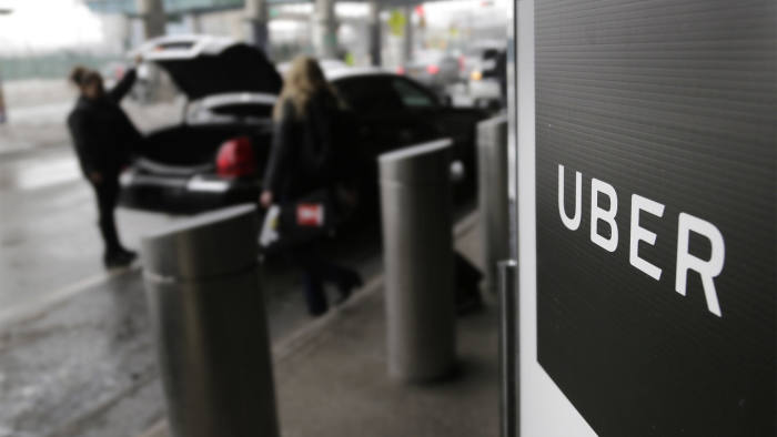 In this March 15, 2017, file photo, a sign marks a pick up point for the Uber car service at LaGuardia Airport in New York. (AP Photo/Seth Wenig, File)
