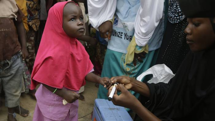 In this photo taken on Sunday, Aug. 28, 2016, a health official inks a child finger to indicate she has been administered with a polio vaccine, at a camp of people displaced by Islamist extremist in Maiduguri, Nigeria. An emergency polio vaccination campaign aimed at reaching 25 million children this year has begun in parts of Nigeria newly freed from Boko Haram Islamic extremists, with fears that many more cases of the crippling disease are likely to be found. (AP Photo/Sunday Alamba)