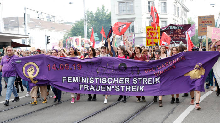 Protesters carry banners and placards at a demonstration during a women's strike (Frauenstreik) in Zurich, Switzerland June 14, 2019. REUTERS/Arnd Wiegmann - RC11FF92F000