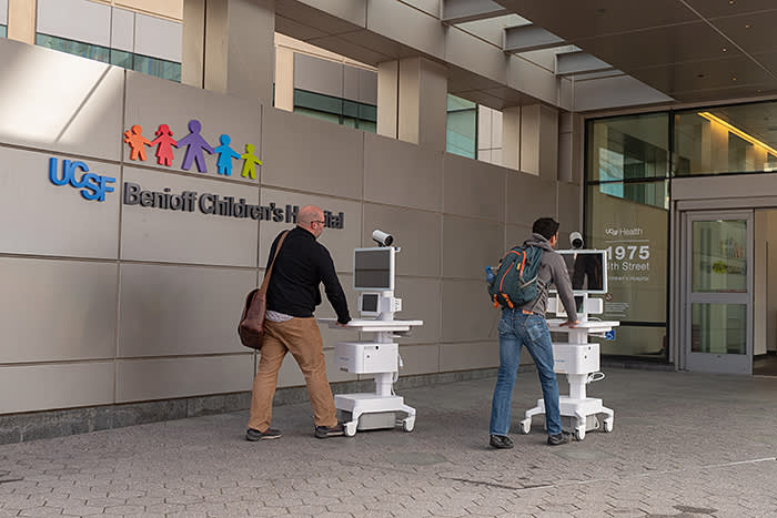 Two staff members wheel Amwell telemedicine carts into the entrance of the University of California San Francisco (UCSF) Benioff Children's Hospital in Mission Bay, San Francisco, California during an outbreak of the COVID-19 coronavirus, March 16, 2020. As a result of the outbreak, patients are increasingly being asked to conduct telemedicine appointments to avoid infecting healthcare workers. (Photo by Smith Collection/Gado/Getty Images)