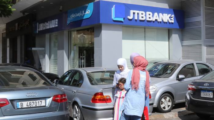 People walk past a branch of Jammal Trust Bank in the Beirut's Hamra street on August 30, 2019, in the Lebanese capital. - The United States on August 29, announced sanctions in Lebanon and Oman aimed at shutting down financing to the Iranian-backed group Hezbollah and the Palestinian Hamas militants. Powerful US financial sanctions were imposed on the Jammal Trust Bank in Lebanon, which was accused of acting as a key financial institution for Hezbollah, which opposes US ally Israel. (Photo by ANWAR AMRO / AFP)ANWAR AMRO/AFP/Getty Images