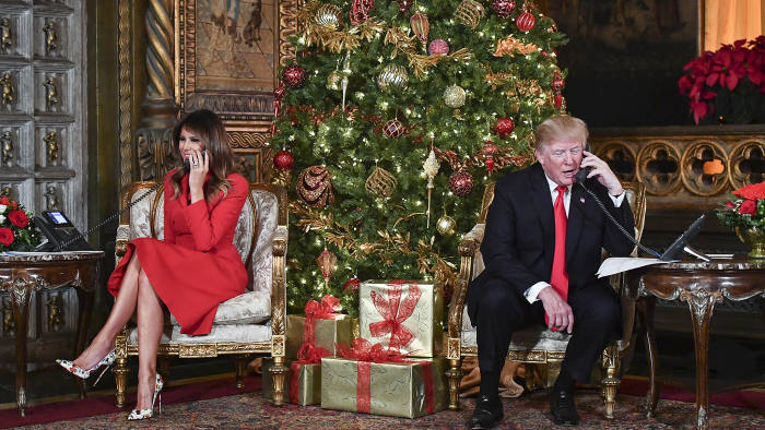 TOPSHOT - US President Donald J. Trump and the First Lady Melania Trump participate in NORAD Santa Tracker phone calls at the Mar-a-Lago resort in Palm Beach, Florida on December 24, 2017. (Photo by Nicholas Kamm / AFP) (Photo credit should read NICHOLAS KAMM/AFP/Getty Images)