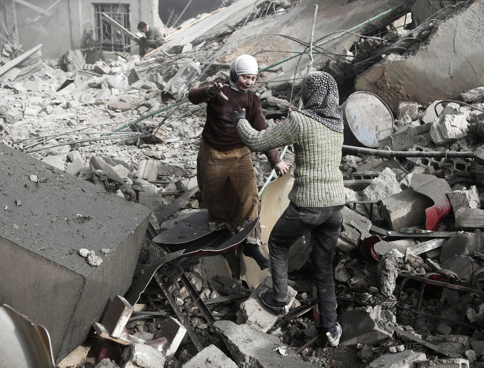 TOPSHOT - CORRECTION - EDITORS NOTE: Graphic content / Two Syrian sisters run across the rubble to embrace after finding each other alive following an air strike on Hamouria, in the besieged rebel-held Eastern Ghouta area near Damascus, on January 9, 2018. Air strikes and artillery fire killed dozens of civilians in the besieged rebel enclave near Damascus targeted by near-daily regime bombardment, a war monitor said. / AFP PHOTO / ABDULMONAM EASSA / The erroneous mention[s] appearing in the metadata of this photo by ABDULMONAM EASSA has been modified in AFP systems in the following manner: [Hamouria] instead of [Saqba]. Please immediately remove the erroneous mention[s] from all your online services and delete it (them) from your servers. If you have been authorized by AFP to distribute it (them) to third parties, please ensure that the same actions are carried out by them. Failure to promptly comply with these instructions will entail liability on your part for any continued or post notification usage. Therefore we thank you very much for all your attention and prompt action. We are sorry for the inconvenience this notification may cause and remain at your disposal for any further information you may require.ABDULMONAM EASSA/AFP/Getty Images