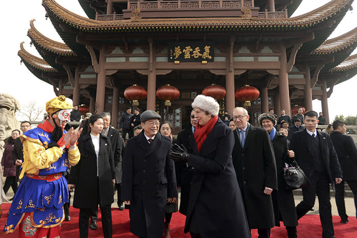 British Prime Minister Theresa May applause to a performer after she watches an opera show with her husband Philip May during a tour to the ancient Huanghelou Tower in Wuhan in central China's Hubei province, Wednesday, Jan. 31, 2018. (Chinatopix via AP)