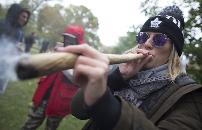 TOPSHOT - A woman smokes a marijuana cigarette during a legalization party at Trinity Bellwoods Park in Toronto, Ontario, October 17, 2018. - Nearly a century of marijuana prohibition came to an end Wednesday as Canada became the first major Western nation to legalize and regulate its sale and recreational use. Scores of customers braved the cold for hours outside Tweed, a pot boutique in St John's, Newfoundland that opened briefly at midnight, to buy their first grams of legal cannabis.In total, Statistics Canada says 5.4 million Canadians will buy cannabis from legal dispensaries in 2018 -- about 15 percent of the population. Around 4.9 million already smoke. (Photo by Geoff Robins / AFP)GEOFF ROBINS/AFP/Getty Images