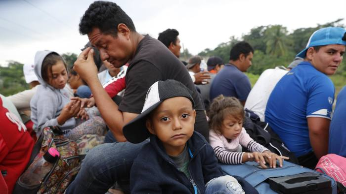 Central American migrants, part of the caravan hoping to reach the U.S. border, get a ride on the bed of a semi flat bed trailer, in Donaji, Oaxaca state, Mexico, Friday, Nov. 2, 2018. The migrants had already made a grueling 40-mile (65-kilometer) trek from Juchitan, Oaxaca, on Thursday, after they failed to get the bus transportation they had hoped for. But hitching rides allowed them to get to Donaji early, and some headed on to a town even further north, Sayula. (AP Photo/Marco Ugarte)