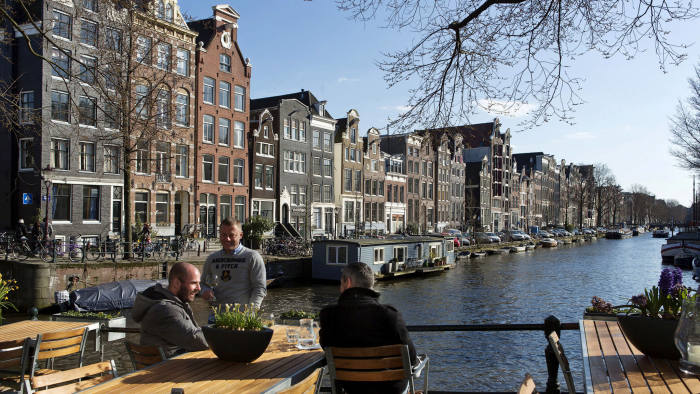 Men enjoy the afternoon sun at the Brouwersgracht canal in Amsterdam, April 2, 2013. REUTERS/Michael Kooren/File Photo - S1AETPSNOQAA