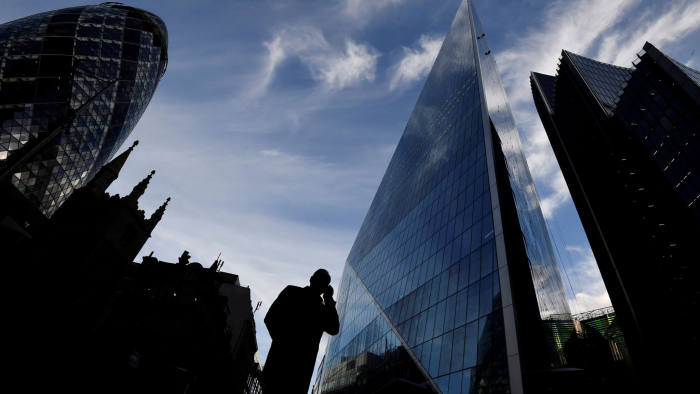 A man speaks on his phone as he walks past The Gherkin and other office buildings in the City of London, Britain November 13, 2018. REUTERS/Toby Melville - RC144545D070