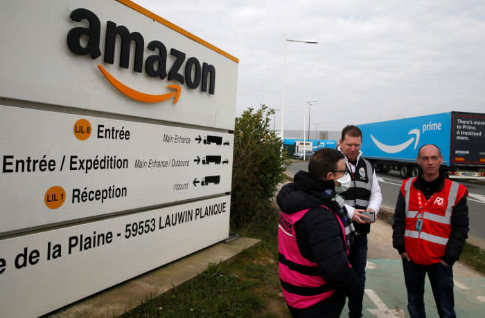 Amazon employees on strike gather outside the Amazon logistics center in Lauwin-Planque, northern France, March 19, 2020. Several hundred employees protested in France, calling on the U.S. e-commerce giant to halt operations or make it easier for employees to stay away during the coronavirus (COVID-19) epidemic. REUTERS/Pascal Rossignol