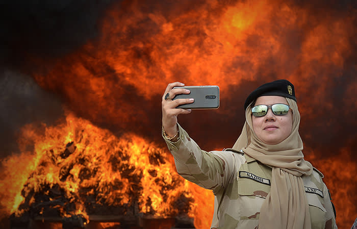 A member of the Pakistani Anti-Narcotic Force (ANF) takes a selfie beside a pile of burning drugs and liquor during a ceremony at the Kacha Ghari army firing range, on the outskirts of Peshawar on October 16, 2018, after the contraband was seized in raids across the province. (Photo by ABDUL MAJEED / AFP)ABDUL MAJEED/AFP/Getty Images