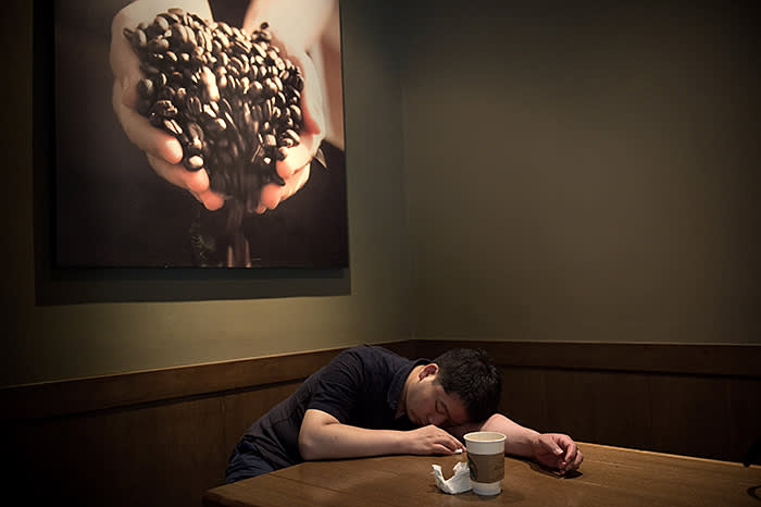 A man takes a nap after drinking a coffee inside a Starbucks in Beijing on June 28, 2017. / AFP PHOTO / NICOLAS ASFOURI (Photo credit should read NICOLAS ASFOURI/AFP/Getty Images)