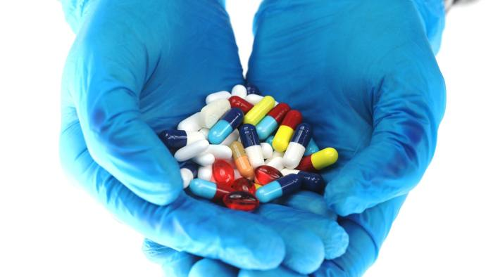 Hands wearing blue surgical gloves hold brightly coloured pharmaceutical medication, including antibiotics, paracetamol, Ibuprofen and cold relief tablets, manufactured by a variety of companies in this arranged photograph in London, U.K., on Friday, April 27, 2018. Pharmaceutical companies may see approval times cut to 14 months vs. 19 and about $370 million of sales brought forward per antibiotic after global regulators aligned rules to combat bacterial resistance. Photographer: Chris Ratcliffe/Bloomberg