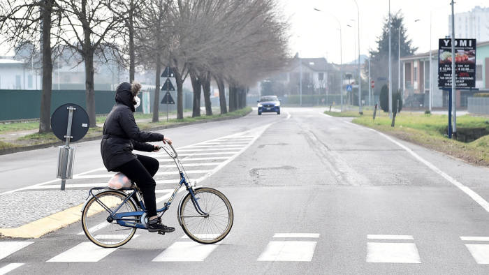 A person wearing a face mask rides a bicycle in the town of Codogno, which has been closed by the Italian government due to a coronavirus outbreak in northern Italy, February 23, 2020. REUTERS/Flavio Lo Scalzo