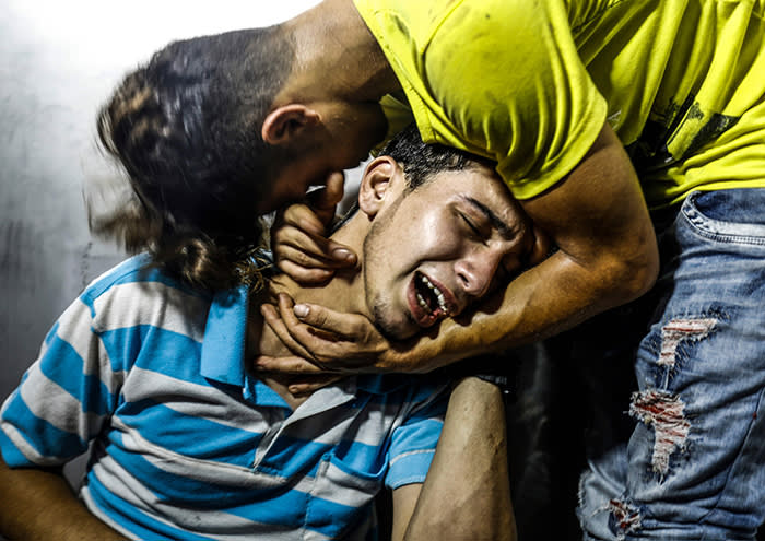 TOPSHOT - Palestinian youths mourn at al-Shifa hospital morgue on July 14, 2018 after two teenagers were killed in one of a series of Israeli raids. Aged 15 and 16, two Palestinians were on a road west of Gaza City when an air strike struck a nearby empty building, the enclave's health ministry said. Israel unleashed a wave of strikes against Gaza on July 14, while scores of rockets were fired back across the border from the territory. / AFP PHOTO / ANAS BABAANAS BABA/AFP/Getty Images