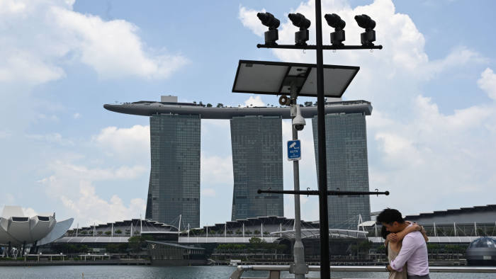 A couple hugs under a closed circuit television (CCTV) surveillance camera in Marina Bay in Singapore on April 2, 2020, as the government slowly tightens restrictions to combat the spread of the COVID-19 novel coronavirus. (Photo by Roslan RAHMAN / AFP) (Photo by ROSLAN RAHMAN/AFP via Getty Images)