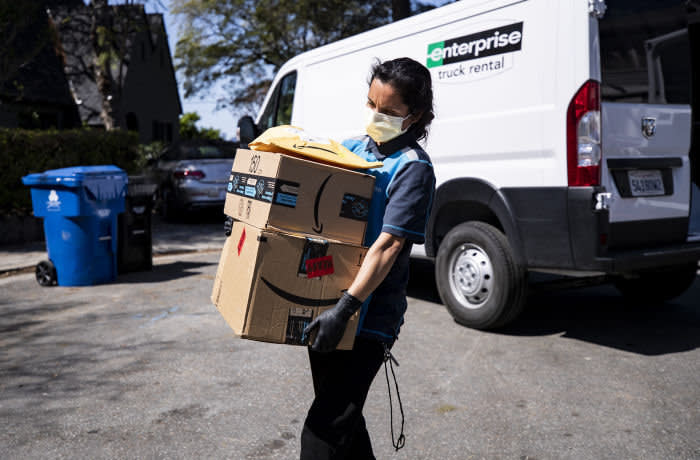 Mandatory Credit: Photo by ETIENNE LAURENT/EPA-EFE/Shutterstock (10595098a) An Amazon delivery woman delivers packages amid the coronavirus pandemic in Los Angeles, California, USA, 26 March 2020. The United States is bracing for the massive economic impact of the ongoing coronavirus pandemic. According to the US Department of Labor there were over three million jobless claims during the week that ended on 21 March. Daily life amid coronavirus pandemic, in Los Angeles, USA - 26 Mar 2020