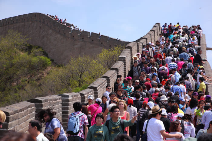 Travel bans worldwide mean scenes like this one, crowds of tourists at the Great Wall of China, are no more