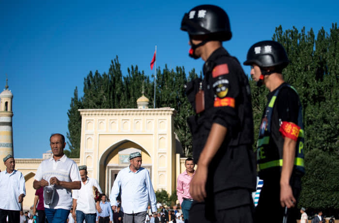 """(FILES) This file photo taken on June 26, 2017 shows police (R) patrolling as Muslims leave the Id Kah Mosque after morning prayer during Eid al-Fitr in Kashgar in China's Xinjiang Uighur Autonomous Region. China's construction of a vast, all-seeing police state in its fractious far west has triggered a government spending spree worth billions to firms providing a hi-tech network of cameras and """"re-education centres"""". The surveillance machine in Xinjiang region has grown exponentially in recent years, used by the ruling Communist Party to guard against what it considers Islamic extremism and separatism in the region. / AFP PHOTO / JOHANNES EISELE / TO GO WITH: CHINA-SECURITY-RIGHTS; Focus by Ben DOOLEYJOHANNES EISELE/AFP/Getty Images"""