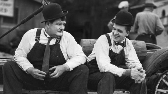 Stan Laurel (1890 - 1965) the stage name of Arthur Stanley Jefferson, the British born comedian and Oliver Hardy (1892 - 1957) the portly American comedian are resting in between scenes during the filming of the Hal Roach production of 'Towed In A Hole', directed by George Marshall. (Photo by Hulton Archive/Getty Images)