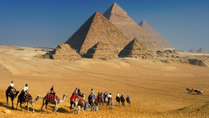 BHW3PM Tourists riding camels at the Pyramids of Giza, Cairo, Egypt.. Image shot 11/2009. Exact date unknown.