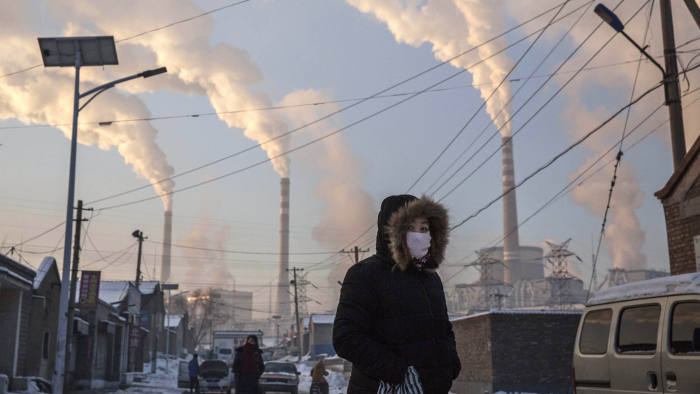 SHANXI, CHINA -NOVEMBER 26: (CHINA, HONG KONG, MACAU, TAIWAN OUT) Smoke billows from stacks as a Chinese woman wears as mask while walking in a neighborhood next to a coal fired power plant on November 26, 2015 in Shanxi, China. A history of heavy dependence on burning coal for energy has made China the source of nearly a third of the world's total carbon dioxide (CO2) emissions, the toxic pollutants widely cited by scientists and environmentalists as the primary cause of global warming. China's government has publicly set 2030 as a deadline to reach the country's emissions peak, and data suggest the country's coal consumption is already in decline. The governments of more than 190 countries are expected to sign an agreement in Paris to set targets on reducing carbon emissions in an attempt to forge a new global agreement on climate change. (Photo by Kevin Frayer/Getty Images)