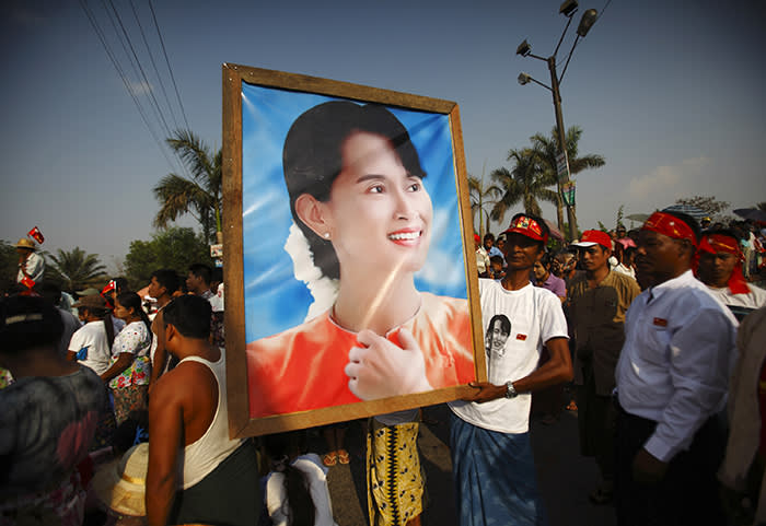 Supporters of Myanmar's pro-democracy leader Aung San Suu Kyi holds her portrait as they wait for her to arrive for an election campaign at Seikkan Township in Yangon March 21, 2012. REUTERS/Staff (MYANMAR - Tags: POLITICS) - GM1E83L1RKH01