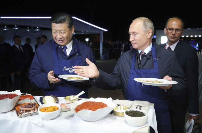 Russian President Vladimir Putin, right, gestures as he and Chinese President Xi Jinping select food, as they visit an exhibition during the Eastern Economic Forum in Vladivostok, Russia, Tuesday, Sept. 11, 2018. (Sergei Bobylev/TASS News Agency Pool Photo via AP)