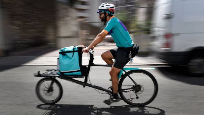 A biker working for the Food delivery service Deliveroo cycles off to deliver an order on July 3, 2018 in Saint-Ouen, outside Paris. - Deliveroo, which delivers home-made dishes from neighborhood restaurants, has opened shared kitchens in Saint-Ouen, in the Paris region, enabling restaurateurs to test a new market, a concept that it is declining around the world. (Photo by GERARD JULIEN / AFP) (Photo credit should read GERARD JULIEN/AFP/Getty Images)