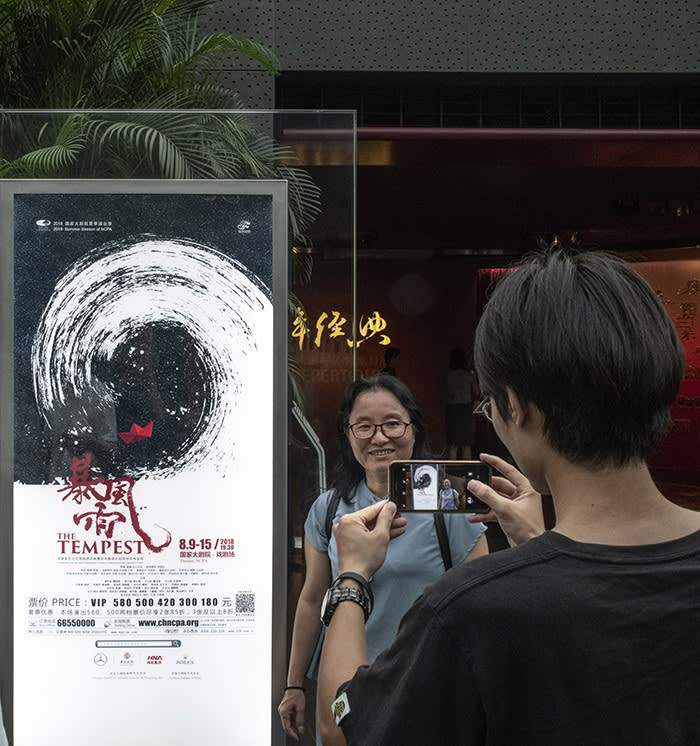 Beijing August 15th, 2018 At the National Centre for Performing Arts, spectators taking souvenir photos with a poster of a a Chinese Production of Shakespeare's The Tempest, before the performance. Gilles SabriÈ for The Financial Times