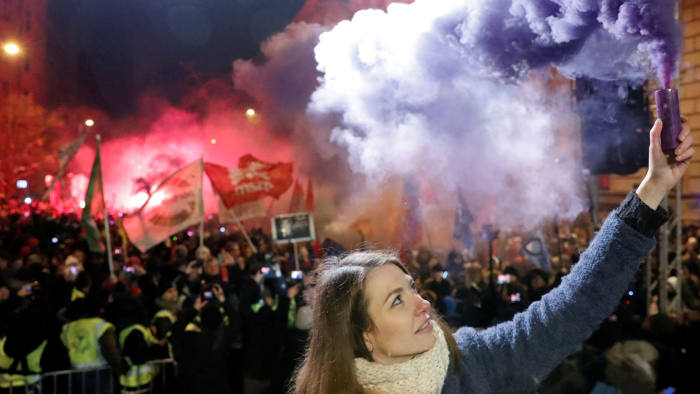 Anna Donath, Vice President of the opposition party Momentum Movement, holds a flare during a protest against a proposed new labor law, billed as the