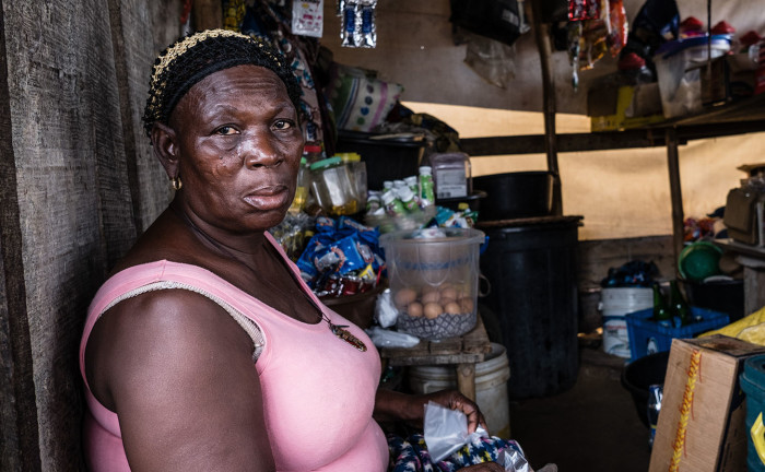 In community of Isale Ijebu in Ajah, Lagos; Mary Kunnu, Tinu's mother who lives with her daughter after being forcibly removed from their ancestral home in Otodo Gbame, sits down in her shop
