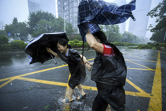 In this photo released by Xinhua News Agency, people with umbrellas walk against strong winds from Typhoon Mangkhut at Nanshan District in Shenzhen, south China's Guangdong Province, Sunday, Sept. 16, 2018. Hong Kong and southern China hunkered down as strong winds and heavy rain from Typhoon Mangkhut lash the densely populated coast. The biggest storm of the year left at least more than dozens dead from landslides and drownings as it sliced through the northern Philippines. (Mao Siqian/Xinhua via AP)