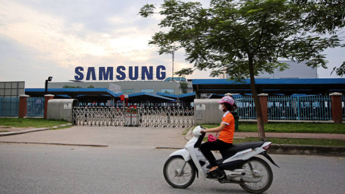 A motorcyclist rides past the Samsung Electronics Vietnam Co. Plant at Yen Phong Industrial Park in Bac Ninh Province, Vietnam, on Thursday, Sept. 1, 2016. Samsung Electronics Co. and its affiliate have built a factory town with 45,000 young workers and hundreds of foreign component suppliers -- a miniature version of the family-run chaebol conglomerates that dominate business back in Korea. The investment has been a windfall for businesses in Bac Ninh -- almost 2,000 new hotels and restaurants opened between 2011 and 2015 according to the provincial statistics office -- helping raise the province's per capita GDP to three times the national average. Photographer: Linh Luong Thai/Bloomberg
