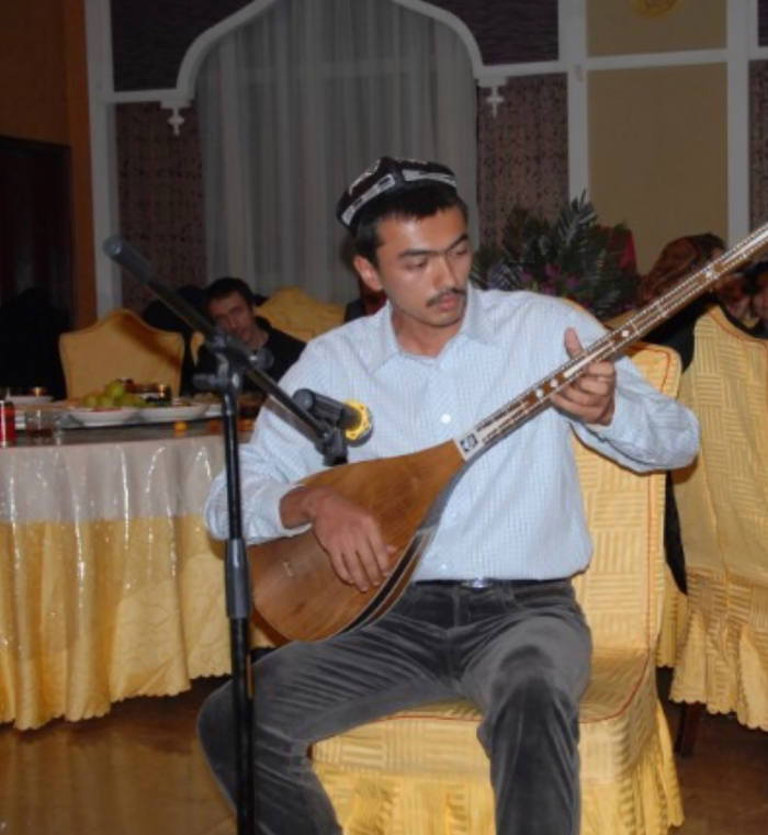 Behram Yarmuhemmed, Gulruy Asqar's nephew, shown here playing the dutar, a traditional Uighur musical instrument. He was forced into an extrajudicial internment camp in 2016